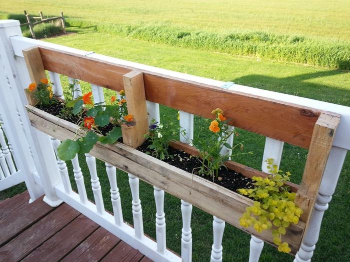 bac a fleur en palette attaché à une clôture de terrasse en teck, idée comment organiser ses plantes espace exterieur