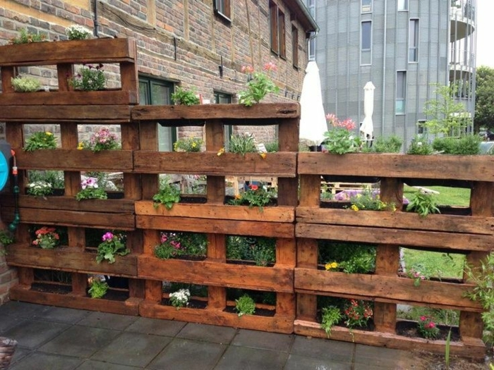 jardiniere palette asymétrique, mur vegetal palette de bois, des fleurs plantés dans le cavités entre les plamches de bois, cloison, mur de sépration