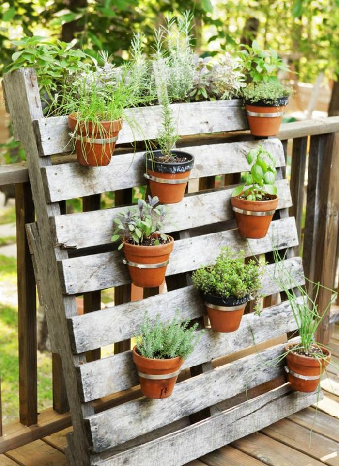 mur vertical adossé à une cloison terrasse en bois, rangement de pots de fleurs sur des planches en bois