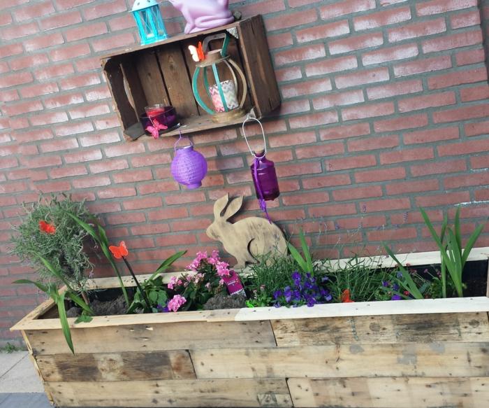 jardiniere en palette avec des fleurs plantées dedans, decoration exterieure printaniere, une etagere en cagette