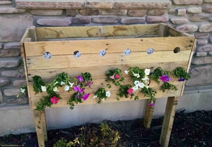 bac a fleur en palette, planches de bois assemblées, des trous avec des fleurs qui y sortent, des galets decoratifs, drainage, mur en briques