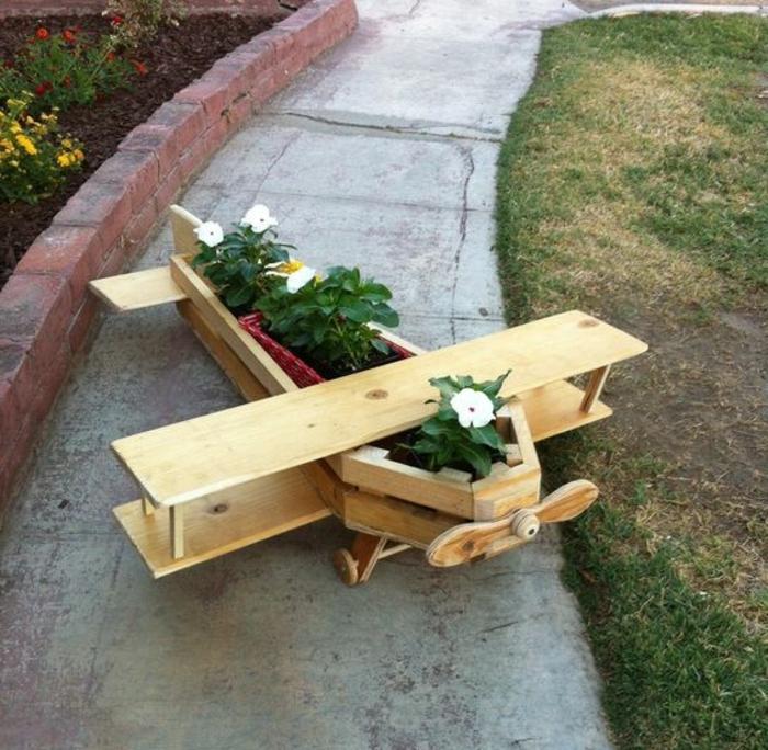jardiniere palette design intéressant, un avion en planches de bois poli, des fleurs plantées, deco jardin exterieur