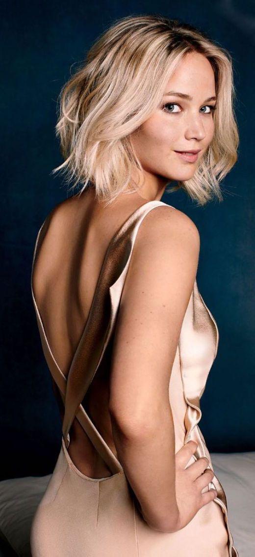jennifer lawrence avec des boucles floues sur des cheveux blond platine, carré plongeant ondulé