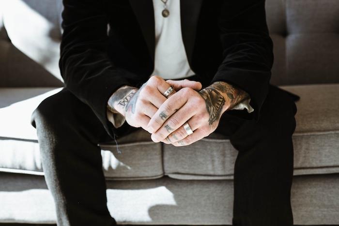 tatouage bras homme, bague homme, collier homme, costume noir, tatouage sur les doigts