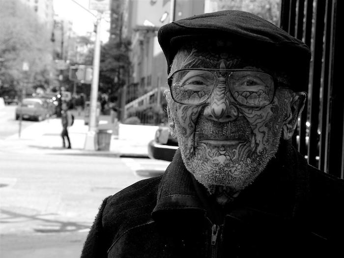 tatouage homme, casquette noire, lunettes de vue, manteau noir, tatouage sur le visage pour homme