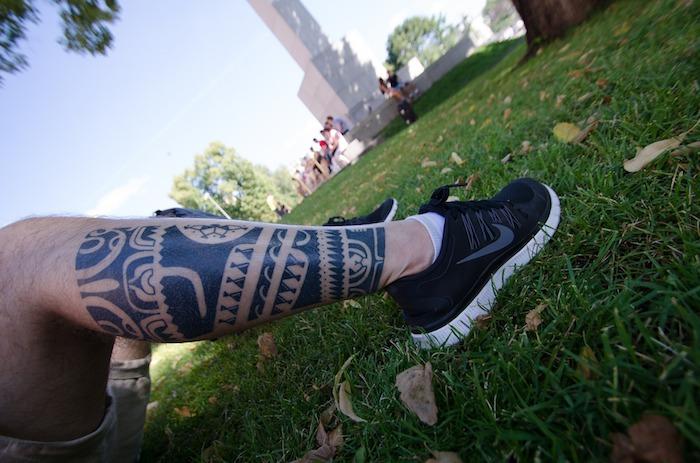 tatouage homme, gazon vert, après midi dans la nature, tatouage polynésien, tattoo sur les jambes, shorts homme beige