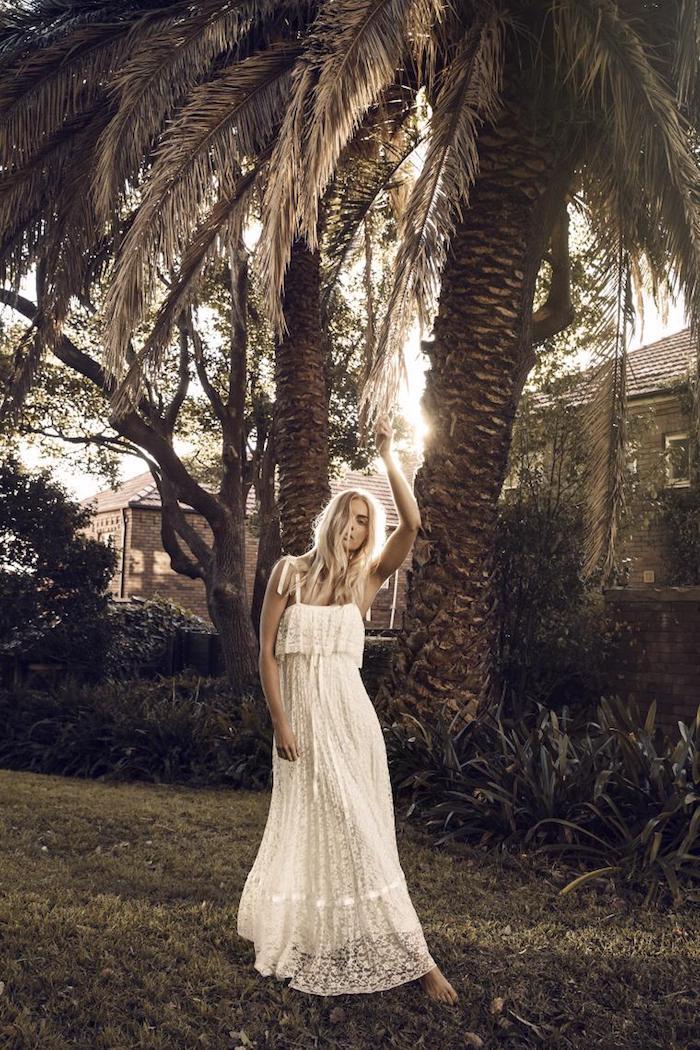 vetement boheme, femme dans le jardin, palmiers, gazon vert, robe longue en dentelle blanche