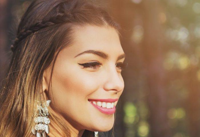 maquillage yeux, cheveux balayage, bijoux avec papillons, lèvres rose, eye liner noir, femme hippie