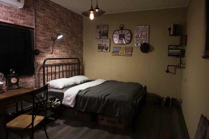 deco industrielle, chaise en bois, horloge, murs en briques, lampes suspendues, étagère à livre, lit noir, murs beige