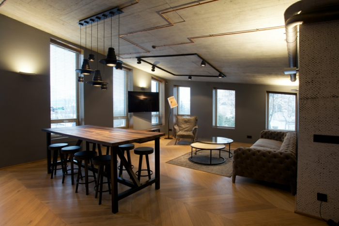 decoration industrielle, parquet en bois, suspension luminaire en fer, table en bois, fauteuil beige, canapé marron