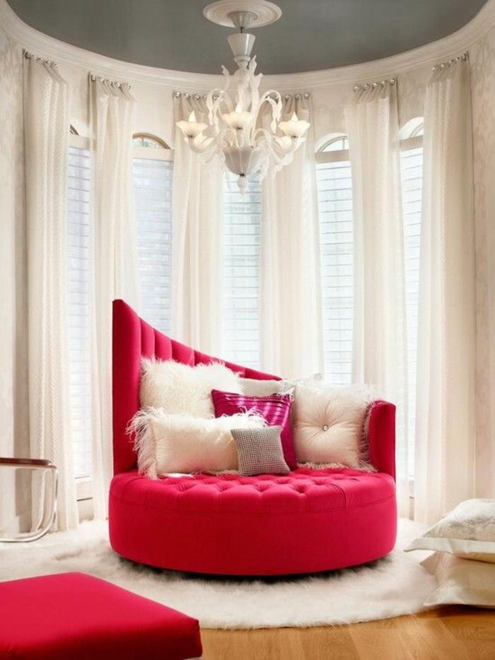 meuble style baroque canapé rond en rouge matelassé avec lustre blanc et des rideaux transparents blancs