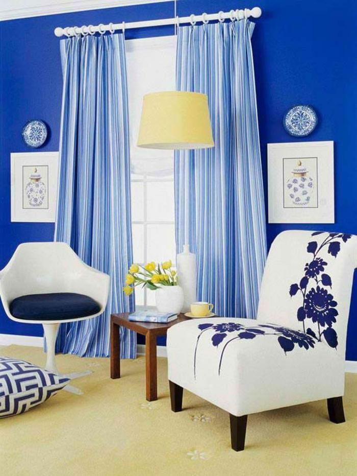 meuble baroc fauteuil sans accoudoirs en blanc et bleu avec des motifs floraux rideaux bleus