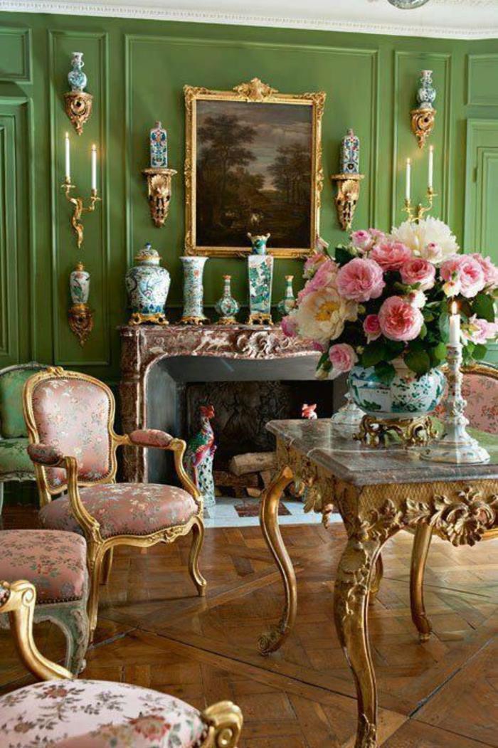 meuble style baroque rococo intérieur aux murs verts avec des vases chinois et des bougeoirs a deux bougies des deux cotes de la cheminée