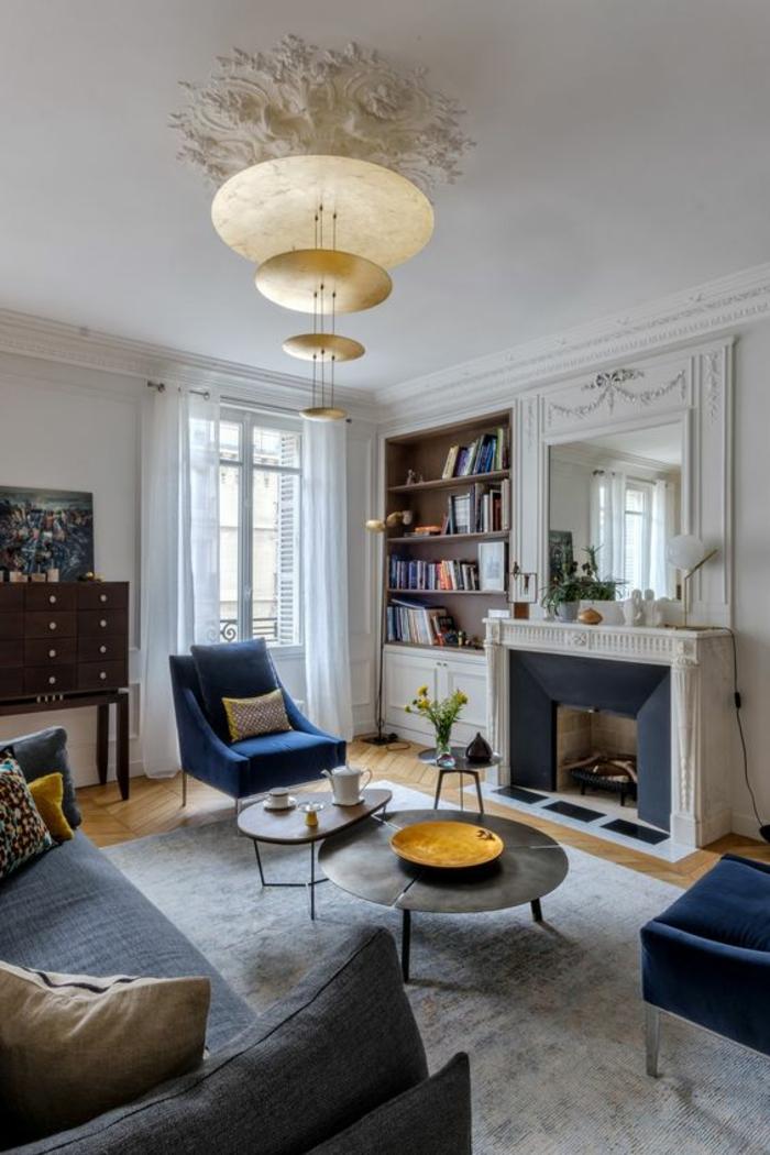 baroque meuble salon avec des fauteuils en bleu indigo et lustre avec quatre grands disques couleur or