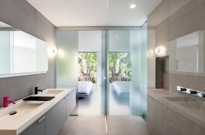 decoration salle de bain, murs taupe poudré, paroi en verre mat, lavabo blanc, porte vers la terrasse