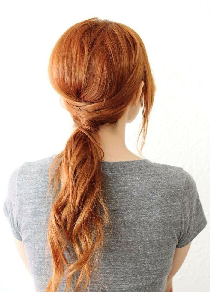 coiffure de femme cheveux roux queue basse avec des meches enroulées autour d'elle