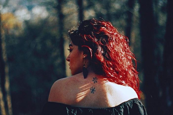tatouage simple et minimaliste de deux flocons de neige stylisés sur le dos, tatouage dos femme à design discret