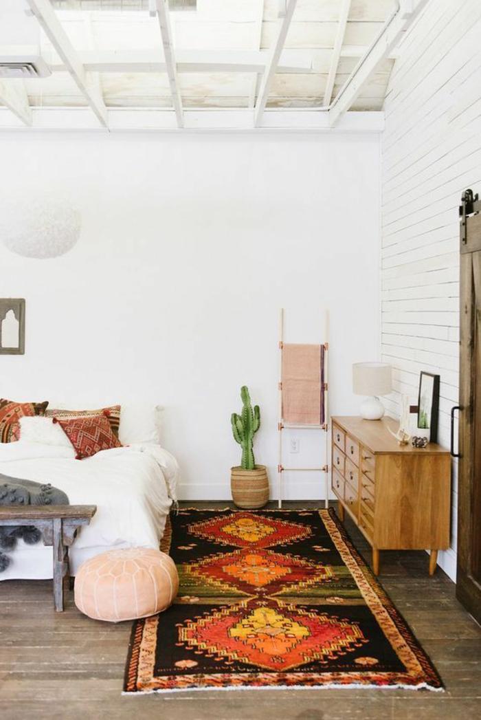 motif aztèque, banquette de lit, commode en bois clair, mur blanc, cactus