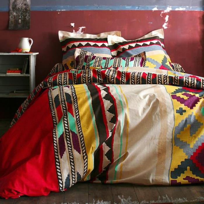 motif aztèque, chambre à coucher, linge de lit en plusieurs couleurs, tête de lit rouge