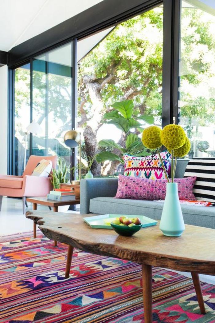 tapis avec motif aztèque, table en bois naturel, vase avec des fleurs, sofa gris et coussins déco