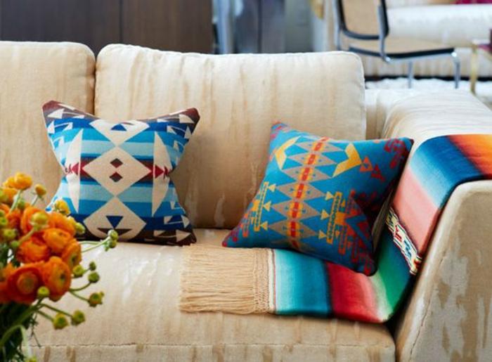 motif aztèque sur les coussins, coussins en bleu et orange, sofa beige, bouquet de fleurs oranges
