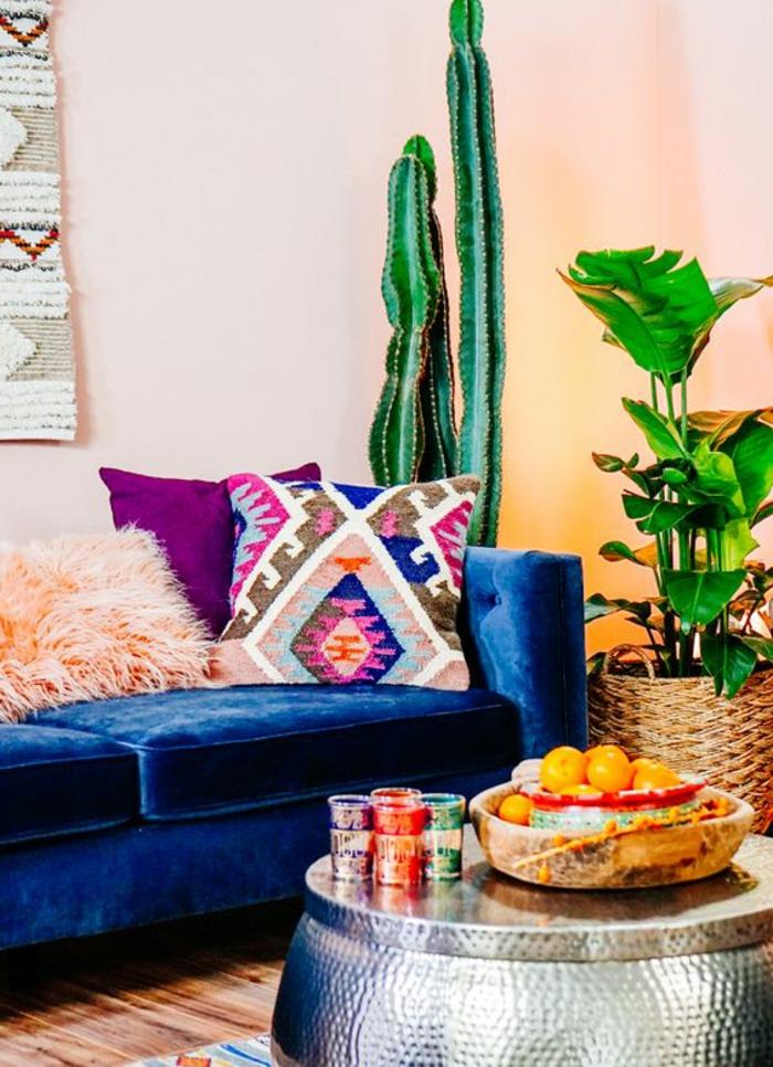 sofa bleu et coussins aux motifs azteques, plantes vertes, tapis mural aztèque