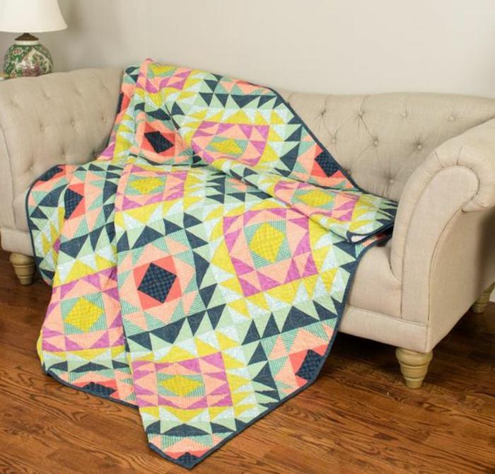 motif aztèque, plaid géometrique à motifs aztèques sur un sofa beige, sol en bois