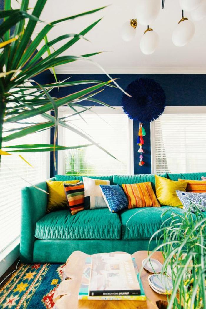 motif azteque, sofa turquoise avec plusieurs coussins jaunes et oranges, palmier décoratif