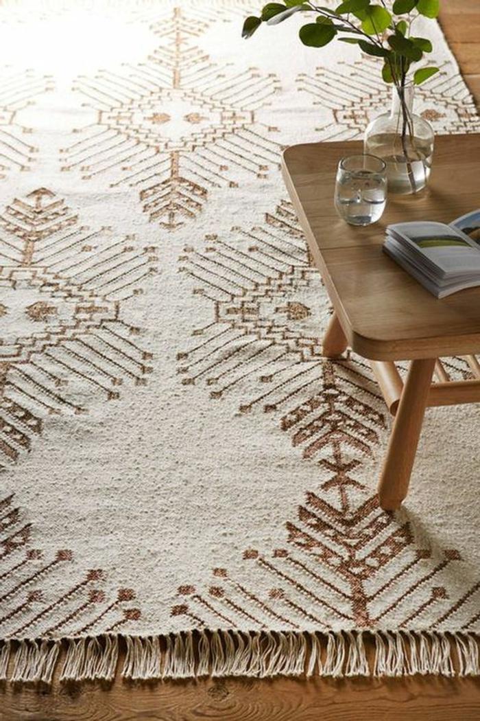 motif azteque, tapis de couleur beige avec motifs aztèques, table en bois