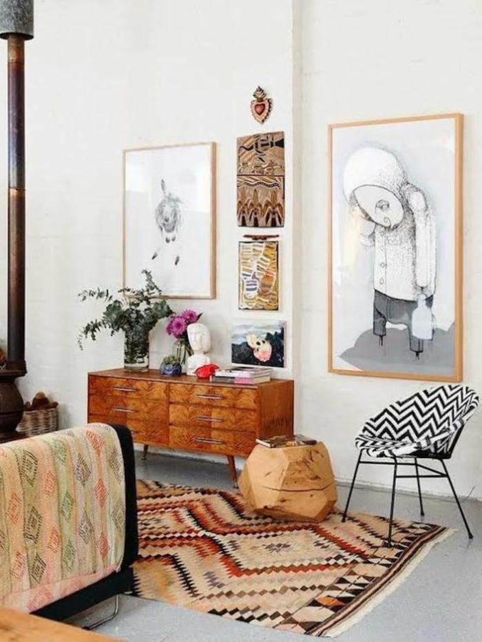 tapis avec motif azteque, commode vintage en bois, tableaux artistiques monochromes