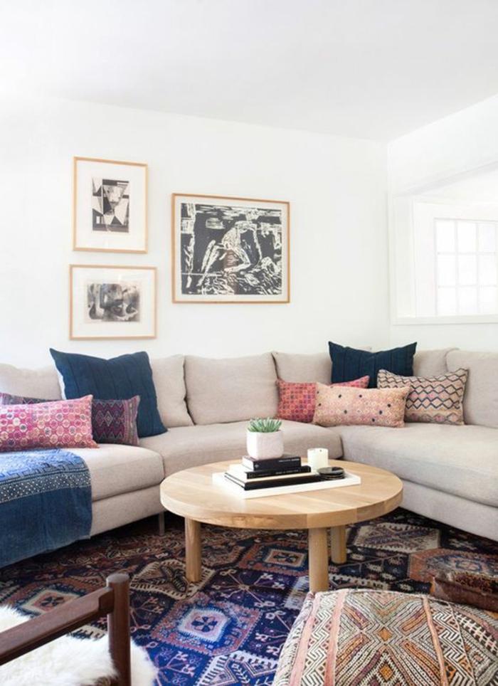 table de salon ronde en bois, sofa d'angle, tapis avec motif azteque, peintures artistiques