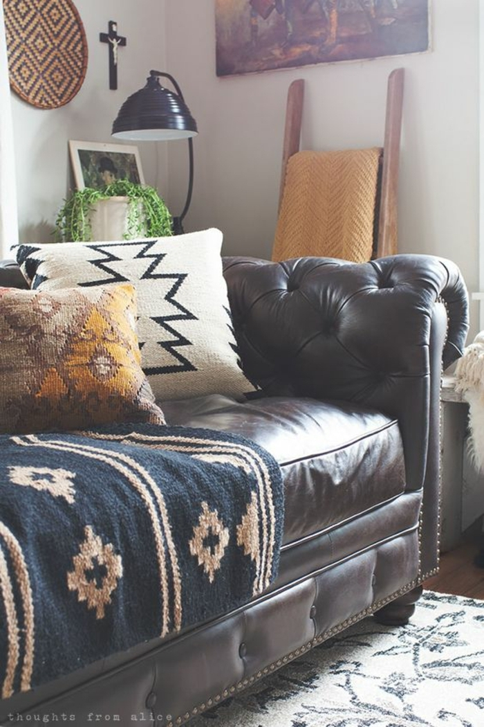 motif azteque, sofa en cuir marron, carpette et coussins ethniques, mur gris pâle