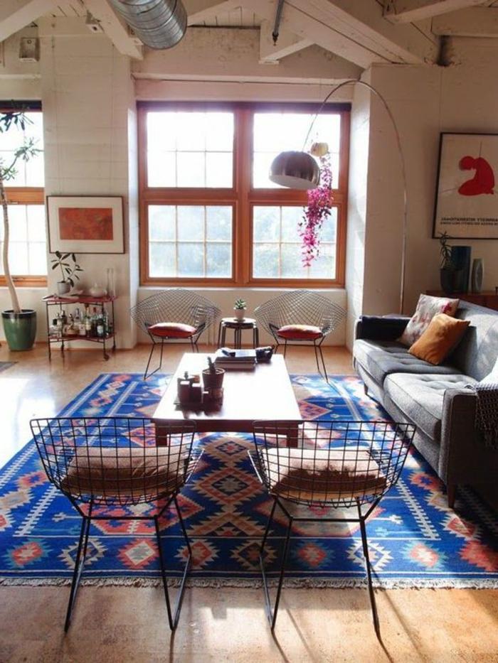 salon à motifs aztèques, chaises métalliques, table en bois rectangulaire, tapis bleu