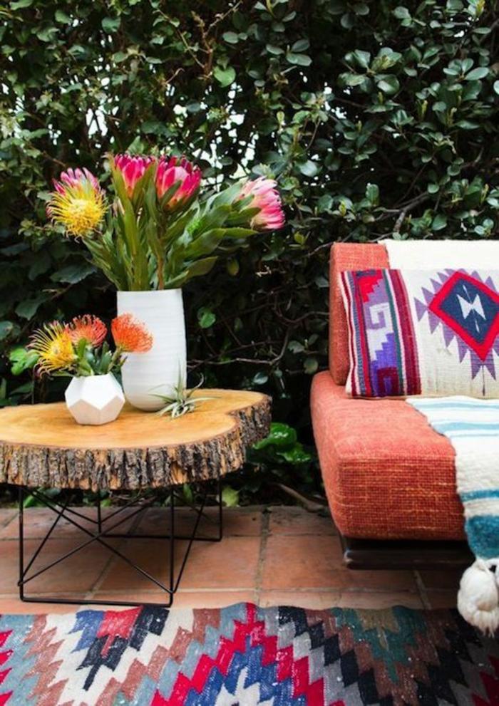 motifs aztèques, sofa orange, table tronc d'arbre, vases avec des fleurs, tapis en rouge et bleu