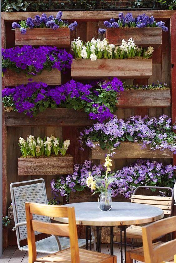jardiniere palette, plusieurs bacs a fleurs, avec des fleurs printanières rangées contre un mur en bois exterieur