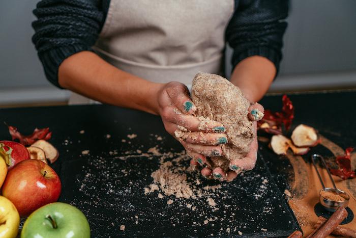 boule de pâte sans gluten à pétrir entre ses mains pour faire tarte aux pommes maison pour son menu équilibré