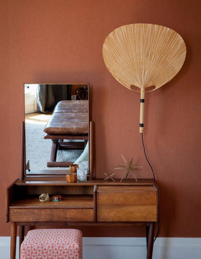 peinture couleur sienne associée à une coiffeuse en bois vintage, un modèle de lampe baladeuse originale en forme d'éventail