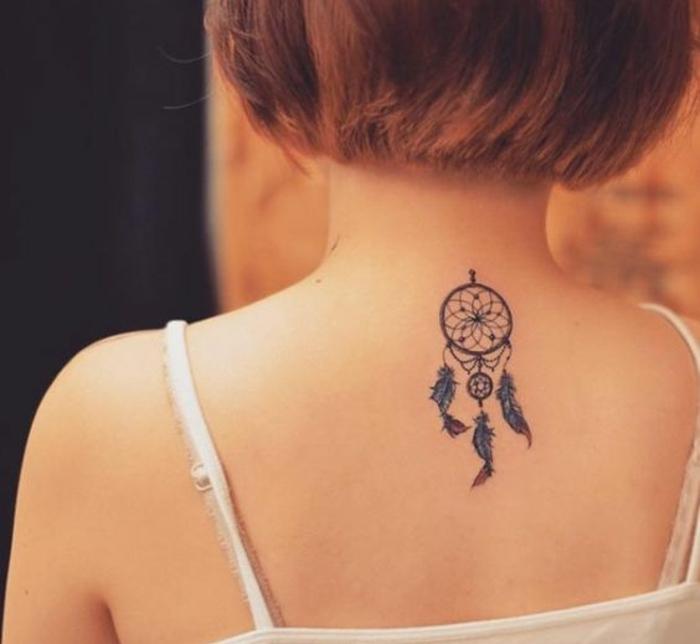tatouage attrape reve sur la nuque, cerceau, filet, plumes bleus aux bouts marron, femme carré court, cheveux rouges