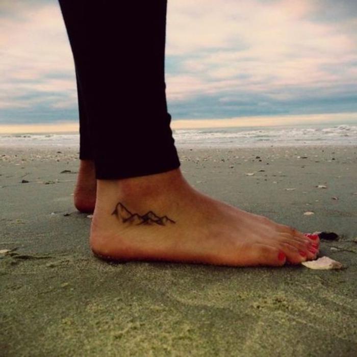 petit tatouage discret, tatouage au piedn une femme sur la plage avec tatoo montagne