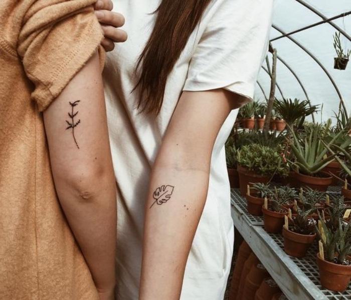 petit tatouage homme, femme, motifs floraux, feuille caduc et un brin de fleur, dessin à l encre noire pour lui et pour elle, tatouage couple