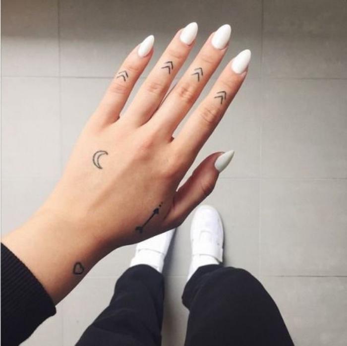 petit tatouage femme, des flèches sur les phalanges des doigts, croissant de lune, flèche et coeur, main poignet, doigt
