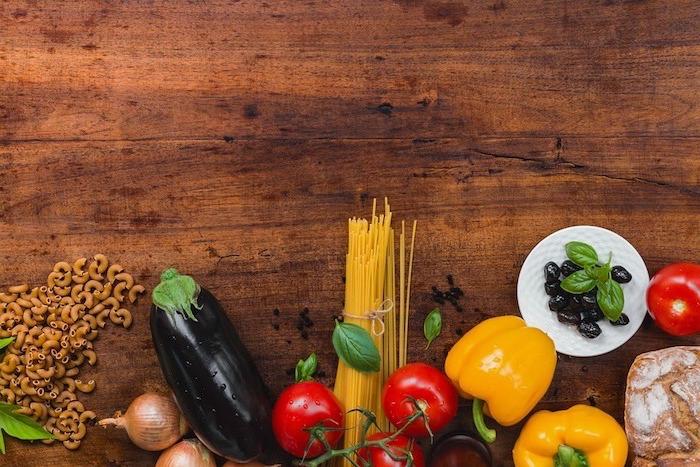 plat équilibré, légumes, poivrons, spaghetties, table en bois, recettes rapides et équilibrées, oignon, olives