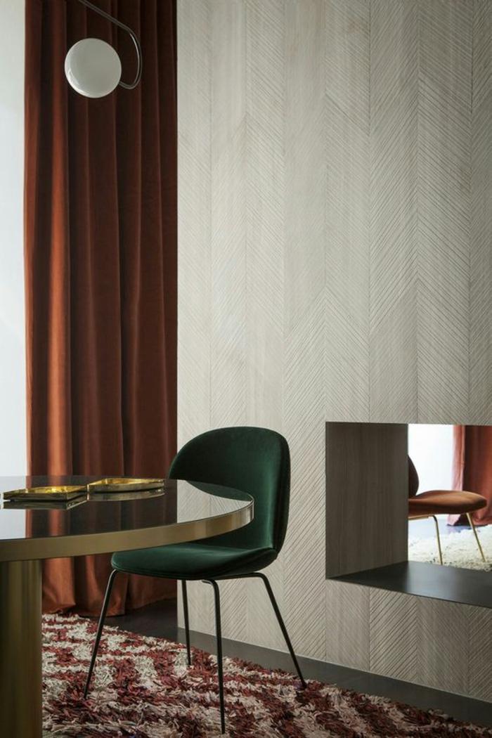 aménagement d'un salon au style contemporain, des rideaux nuance de terre de sienne brûlé associés à une chaise émeraude et une table ronde en métal