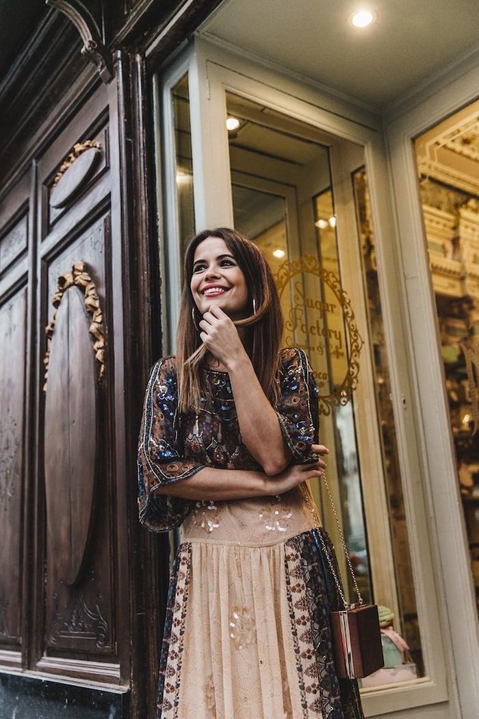 look bohème, femme souriante, éclairage extérieur, porte en bois, cheveux raids, vetement boheme