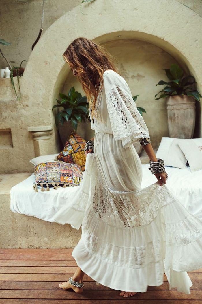 vetement boheme, bracelets métalliques, coussins à motifs ethniques, robe blanche longue, look bohème