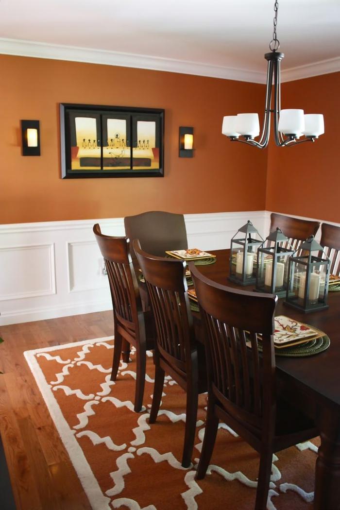 une salle à manger élégant couleur terracotta rehaussée par un soubassement en bois blanc