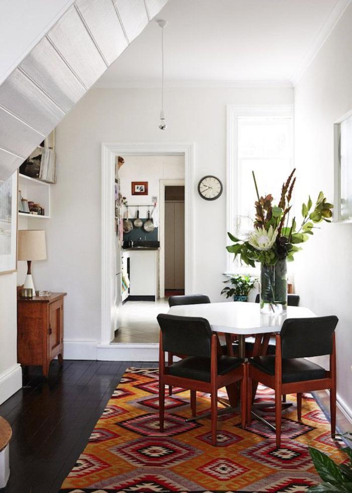 une salle à manger élégante d'esprit vintage, tapis ethnique à motifs géométriques aux tons chauds de rouge et de couleur sienne