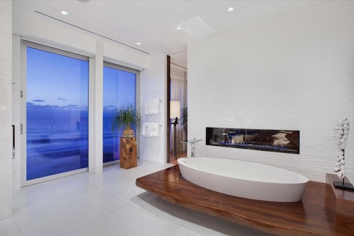 idee salle de bain, dallage blanc, portes coulissantes, vue sur la mer, baignoire blanche, plante verte