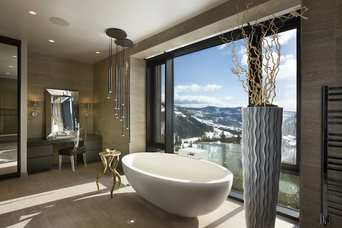 decoration salle de bain, carrelage beige, éclairage LED, porte-serviette métallique, petite table ronde en or