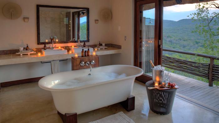 meubles salle de bain, portes coulissantes vers la terrasse, bougies, baignoire blanche, cadre miroir noir